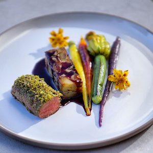 Selle d'agneau en croute d'herbes, légumes glacés en couleurs et fleure de courgette farcie aux champignons